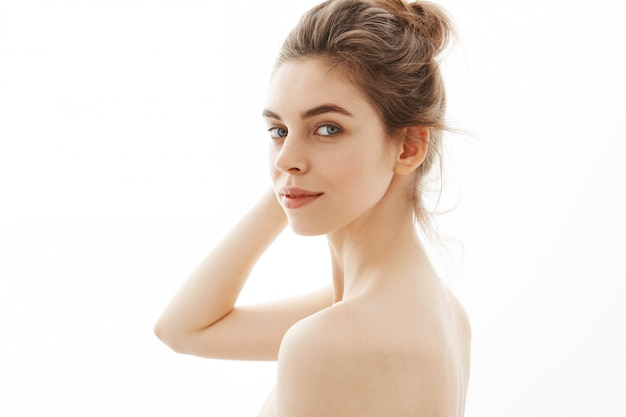 Portrait de jeune jolie femme nue tendre avec chignon sur fond blanc.