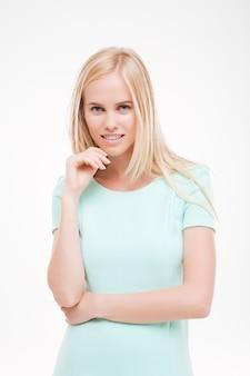 Portrait de jeune jolie femme regardant l'avant, posant sur un mur blanc