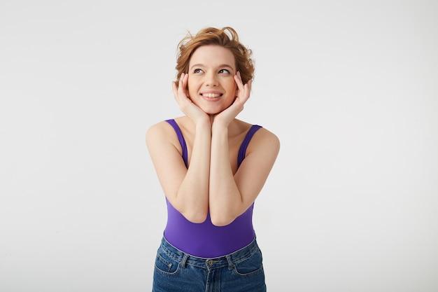 Portrait de jeune jolie fille aux cheveux courts porte en chemise violette, touche le visage avec ses mains, regarde au loin et démontre la beauté naturelle, sourit largement, se dresse sur un mur blanc.