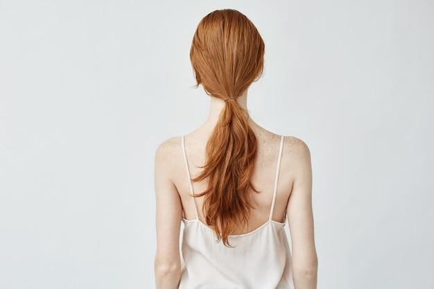 Portrait de jeune jolie fille aux cheveux foxy posant en arrière