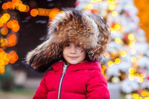 Portrait de jeune jolie fille en bonnet de fourrure traditionnel russe avec oreillettes et veste d'hiver rouge sur fond de noël jour venteux.