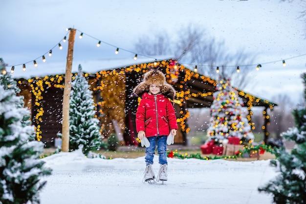 Portrait de jeune jolie fille en bonnet de fourrure traditionnel russe avec oreillettes et veste d'hiver rouge et patins blancs posant sur la patinoire