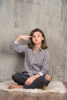 Portrait d'une jeune jolie fille en chemise à carreaux pointant sur la tête