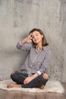 Portrait d'une jeune jolie fille en chemise à carreaux pointant vers la caméra avec deux doigts.