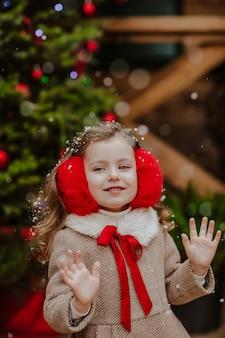 Portrait de jeune jolie fille en manteau d'hiver et cache-oreilles rouges posant sur la terrasse en bois