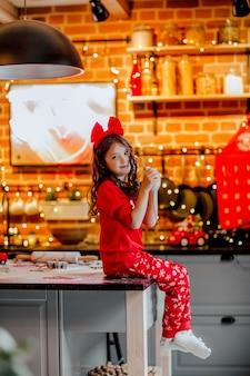 Portrait de jeune jolie fille en pyjama de noël rouge et bandeau tenant petit rat blanc dans la cuisine sur fond de noël.