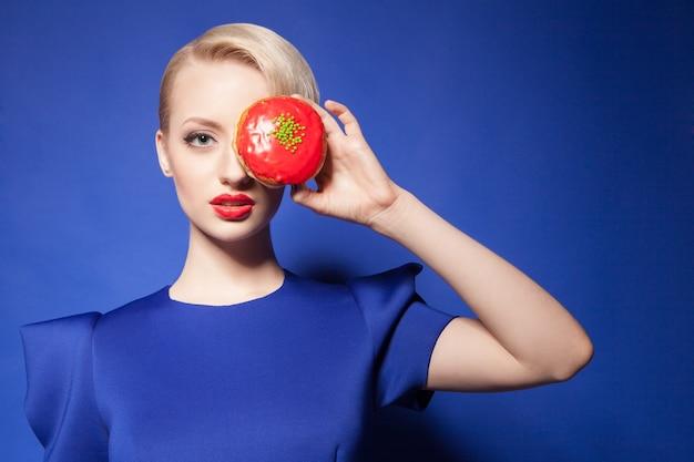 Portrait de jeune jolie mannequin avec des lèvres rouges qui sortent d'un beignet lumineux sur fond bleu