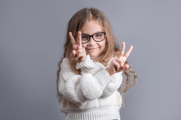 Portrait d'une jeune jolie petite fille aux cheveux blonds en pull montrant v-sign