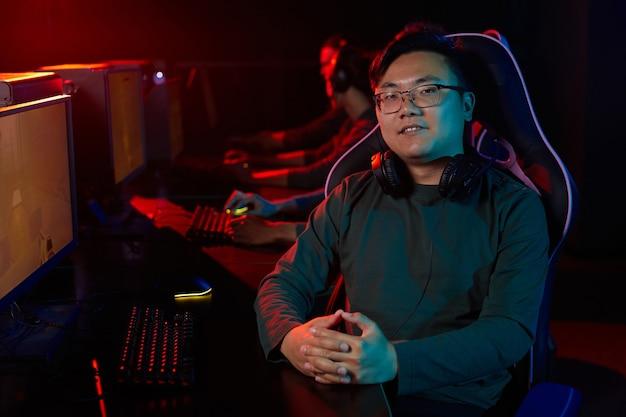 Portrait de jeune joueur asiatique dans les écouteurs souriant à la caméra alors qu'il était assis sur une chaise et jouer à des jeux informatiques