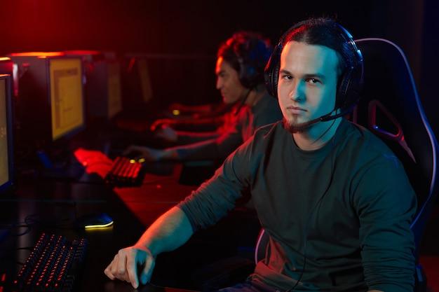 Portrait de jeune joueur au casque assis à la table devant l'ordinateur et jouer à des jeux informatiques