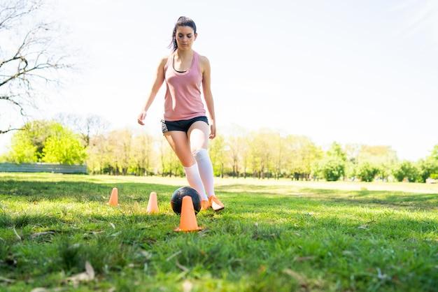 Portrait de jeune joueur de football féminin tournant autour de cônes tout en pratiquant avec ballon sur terrain