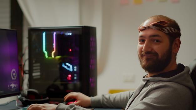 Portrait d'un jeune joueur professionnel assis sur un ordinateur personnel puissant regardant dans la caméra. cyber concentré jouant à un jeu vidéo en ligne de tir à la première personne lors d'un tournoi de jeu
