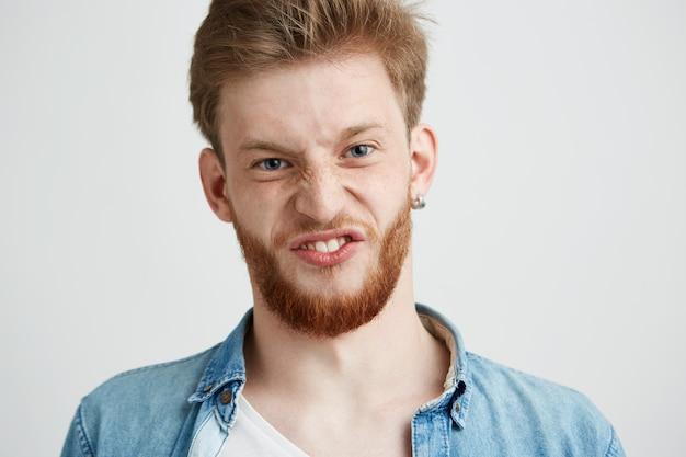 Portrait de jeune joyeux mec joyeux faisant la grimace drôle de visage.