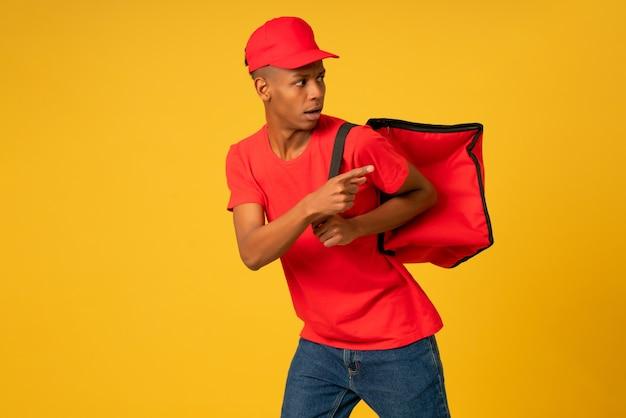 Portrait de jeune livreur vêtu d'un uniforme rouge s'exécutant sur fond isolé. concept de livraison.