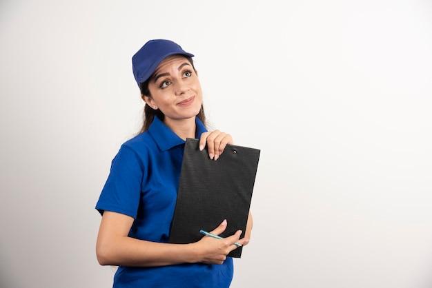 Portrait de jeune livreuse avec presse-papiers. photo de haute qualité