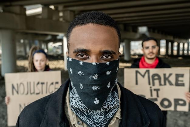 Portrait de jeune manifestant noir en bandana sur le visage debout contre des personnes avec des signes sous le pont