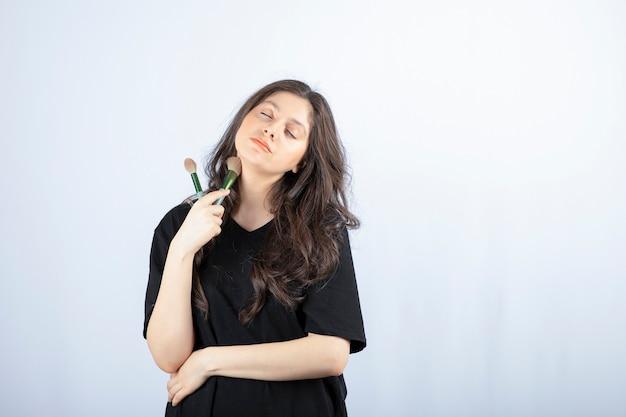 Portrait de jeune mannequin appliquant le maquillage avec un pinceau sur blanc.