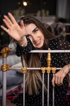 Portrait jeune mannequin assis sur le lit montrant sa main à la caméra.