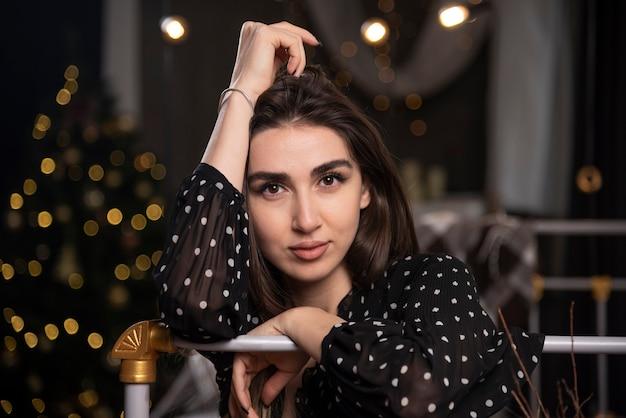 Portrait jeune mannequin assis sur le lit en regardant la caméra.