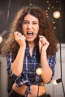 Portrait d'un jeune mannequin en chemise à carreaux mordant un fil de lampes