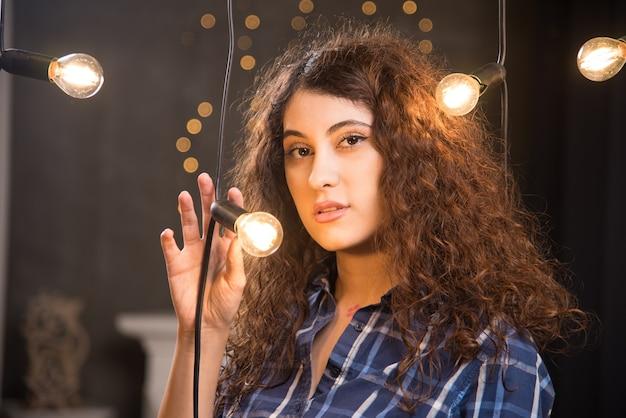 Portrait d'un jeune mannequin en chemise à carreaux posant près de lampes