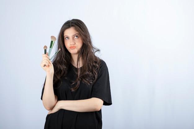Portrait de jeune mannequin avec du maquillage avec des pinceaux debout sur un mur blanc.