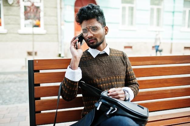 Portrait de jeune mannequin indien élégant pose dans la rue, assis sur un banc avec sac à main et smartphone.