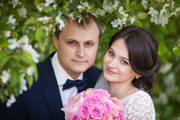 Portrait de jeune marié et mariée avec bouquet de mariage rose dans le jardin fleuri