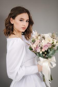 Portrait de jeune mariée avec bouquet de mariage devant photophoot studio backgound gris