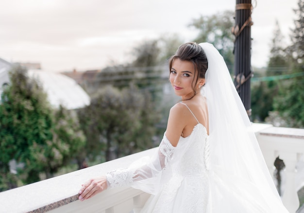 Portrait d'une jeune mariée caucasienne brune souriante sur le balcon qui regarde droit