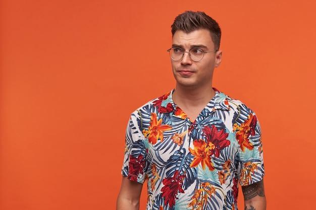 Portrait de jeune mec gai pencive en chemise fleurie, se dresse sur fond orange avec espace copie et regarde ailleurs.