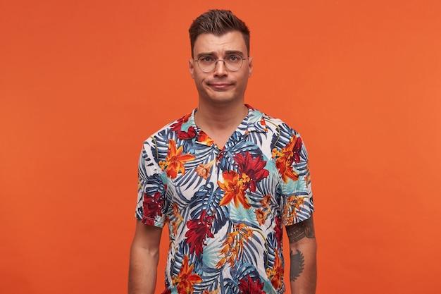 Portrait de jeune mec gai pencive en chemise fleurie, se dresse sur fond orange avec espace copie et semble douteux.
