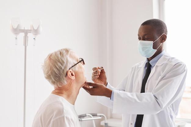 Portrait d'un jeune médecin afro-américain passant le test covid d'un homme âgé dans une chambre d'hôpital