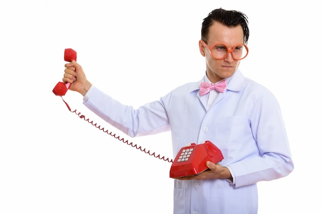Portrait de jeune médecin fou à l'aide de vieux téléphone