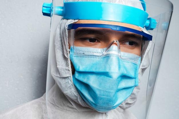 Portrait d'un jeune médecin portant une combinaison epi contre le coronavirus et le covid-19