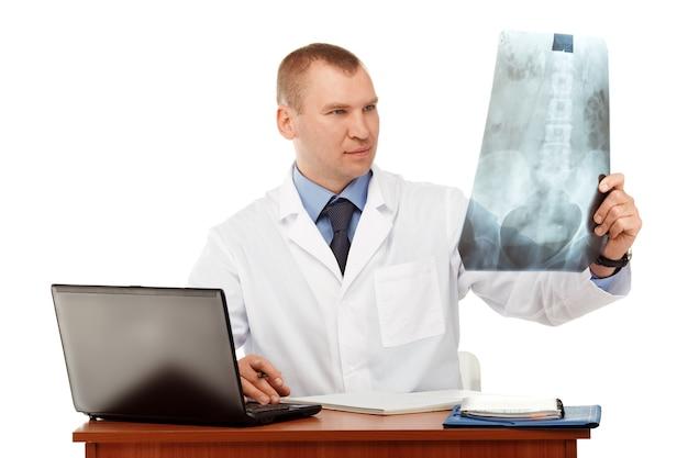 Portrait d'un jeune médecin de sexe masculin dans une blouse blanche contre un blanc