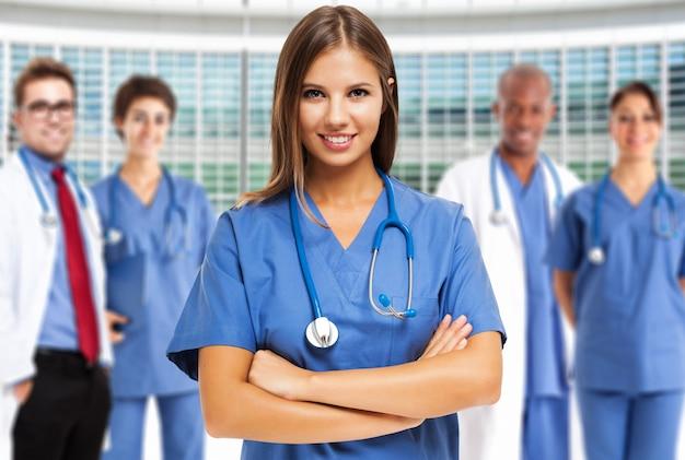 Portrait d'un jeune médecin souriant devant un groupe de travailleurs médicaux