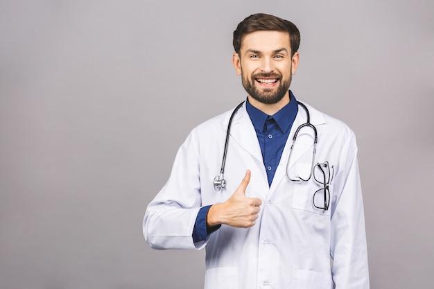 Portrait de jeune médecin souriant gai avec stéthoscope sur le cou en blouse médicale thumbs up.