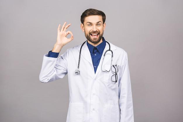 Portrait de jeune médecin souriant gai avec stéthoscope sur le cou en manteau médical signe ok.