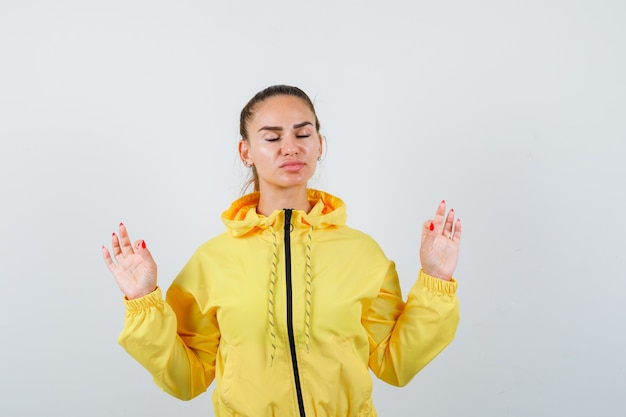 Portrait de jeune méditant en veste jaune et à la vue de face détendue
