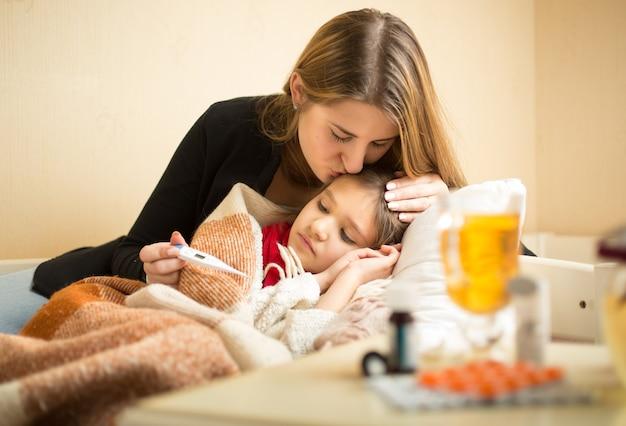 Portrait de jeune mère attentionnée embrassant sa fille malade en tête
