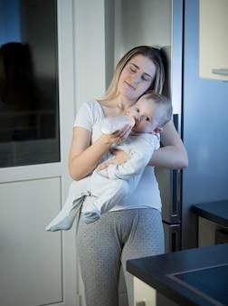 Portrait de jeune mère endormie nourrir son bébé à partir d'une bouteille dans la cuisine la nuit