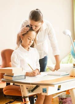 Portrait de jeune mère étreignant et louant sa fille tout en faisant ses devoirs