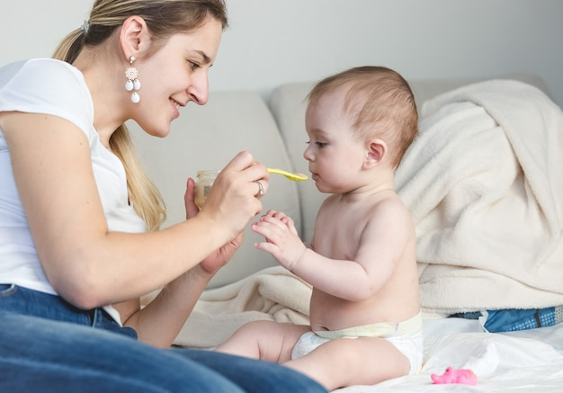 Portrait d'une jeune mère heureuse nourrissant son bébé sur le lit avec une cuillère