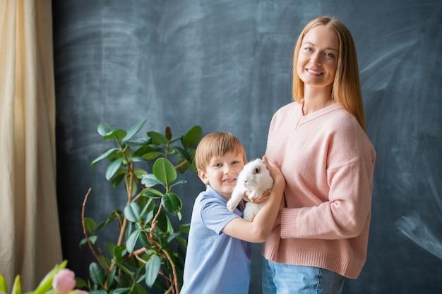 Portrait de jeune mère positive et son fils posant avec lapin contre tableau noir