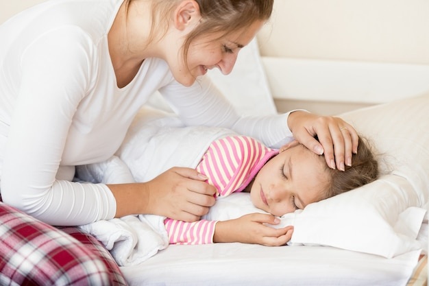 Portrait de jeune mère souriante tenant la main sur la tête des filles endormies