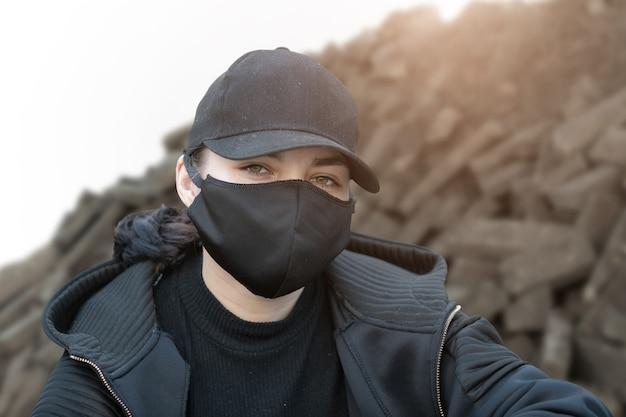 Portrait d'un jeune militant regardant la caméra, dans le contexte d'un tas de pierres