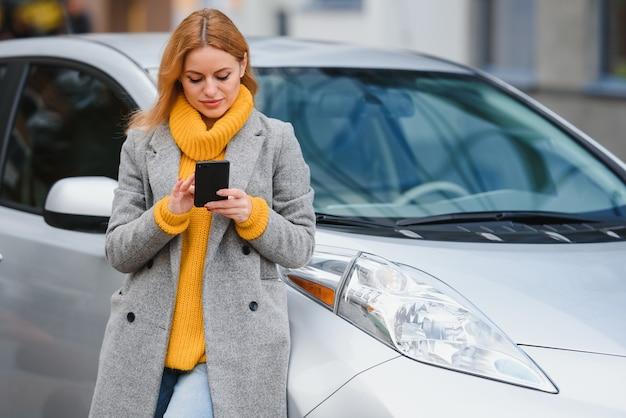 Portrait jeune mode belle femme près de sa voiture, en ville. shopping fille.