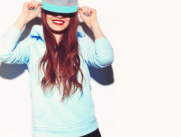 Portrait de jeune modèle femme heureuse avec un maquillage lumineux et des lèvres colorées dans des vêtements d'été hipster isolés sur blanc en casquette de baseball. devenir fou