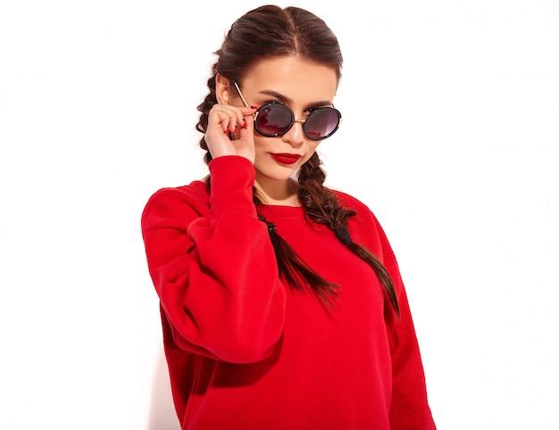 Portrait de jeune modèle femme souriante heureuse avec maquillage lumineux et lèvres colorées avec deux nattes et lunettes de soleil dans des vêtements d'été rouges isolés. derrière les lunettes de soleil mode